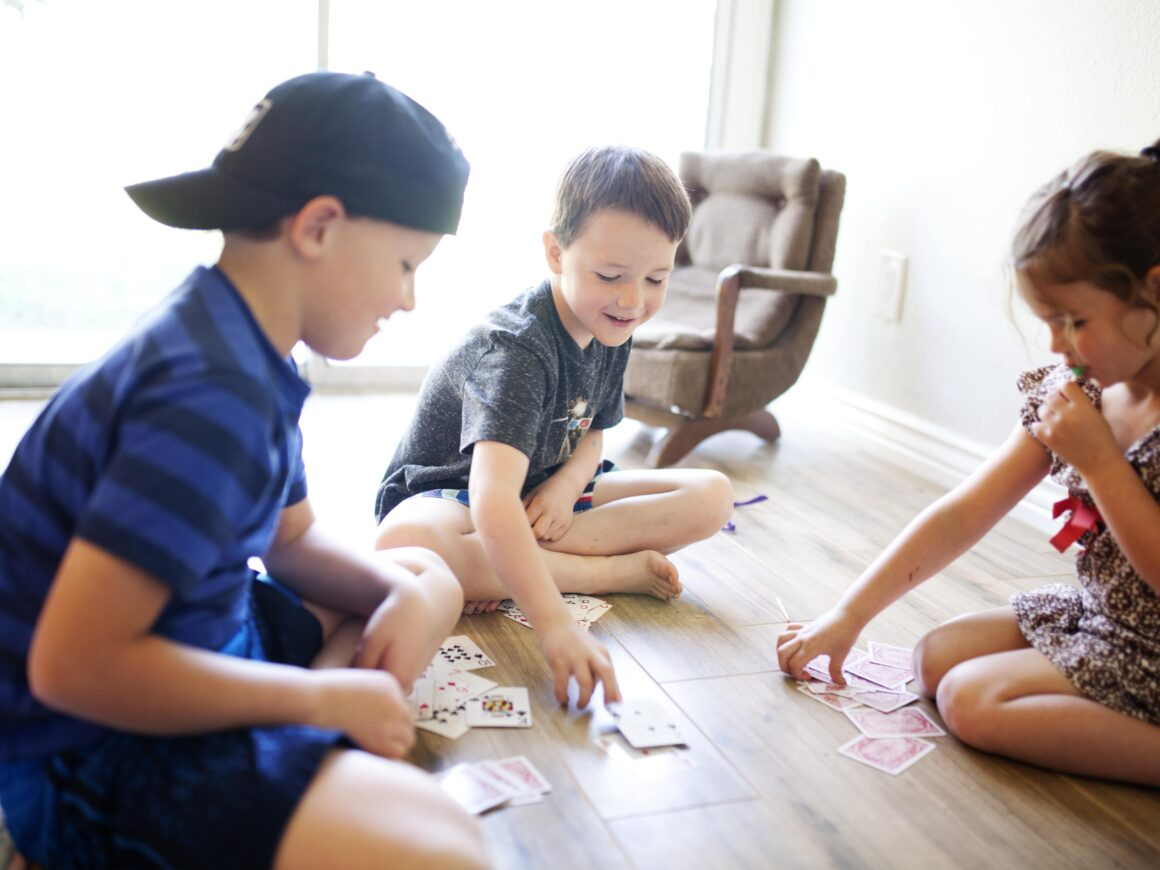 Kids Playing A Game Sitting Down With Cards To Pass The Time