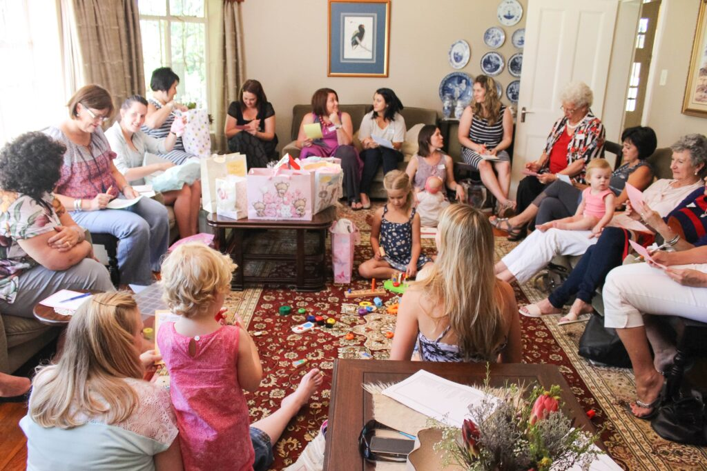 Baby shower guests writing down Baby Shower Memory Game items they remember
