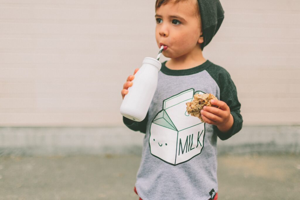 Gorgeous toddler baby boy drinking milk and cookies