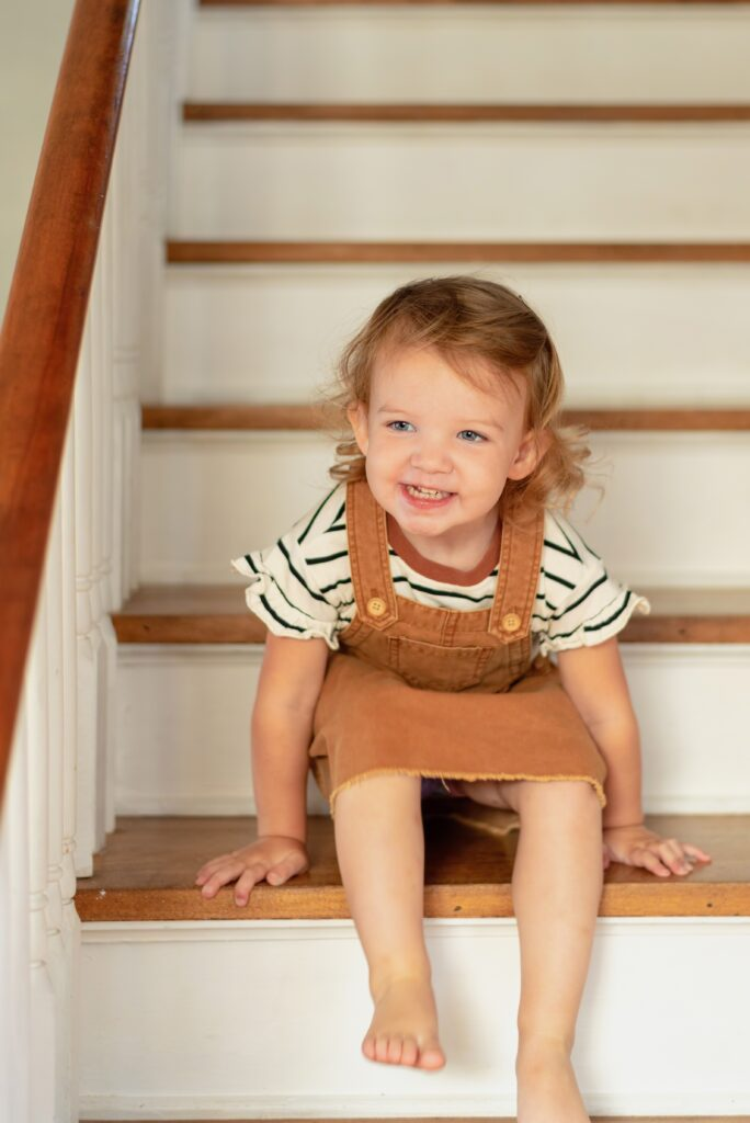 Candid gorgeous picture of a toddler on the stairs laughing