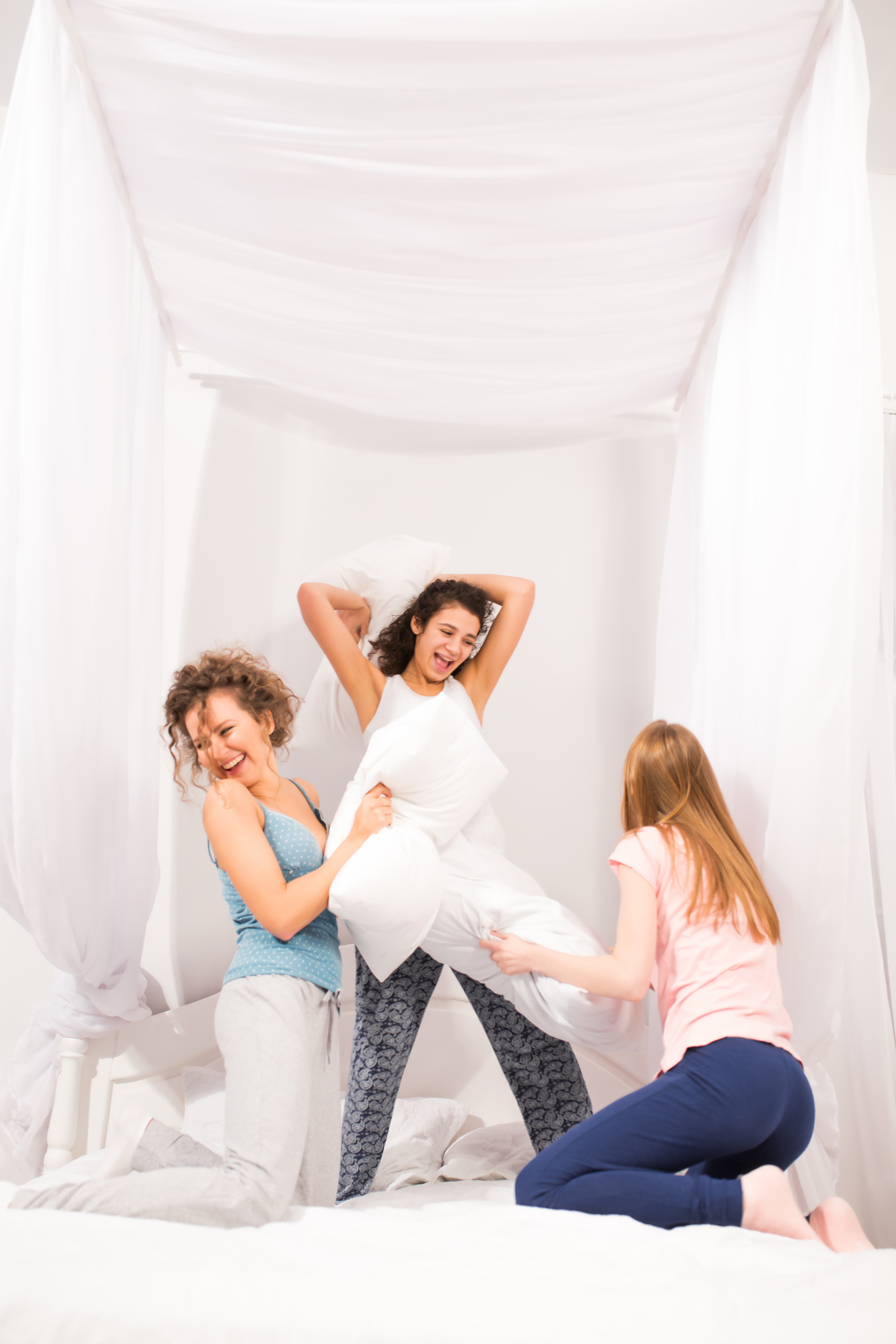 Girls in bed having pillow fight in pajamas at slumber party in bedroom
